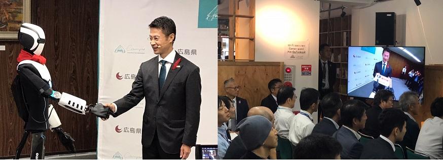 5G×4K映像・音声伝送トライアルイベントにおいて,5G回線を通じてアバターと握手する湯﨑広島県知事