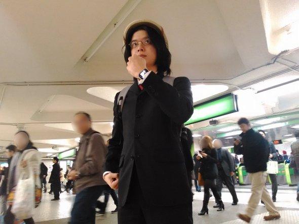 西口改札前で、リモートカメラを使いながら自撮り撮影を行う筆者。通り過ぎる人が思いっきり「なんだこいつ」的な目で見ているのがつらい