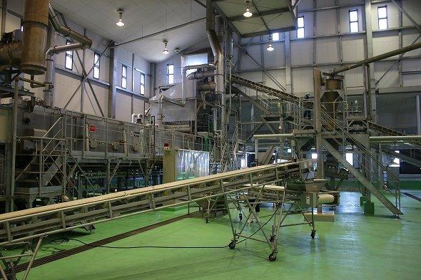 巨大な自動米蒸し器がそびえる工場の様子
