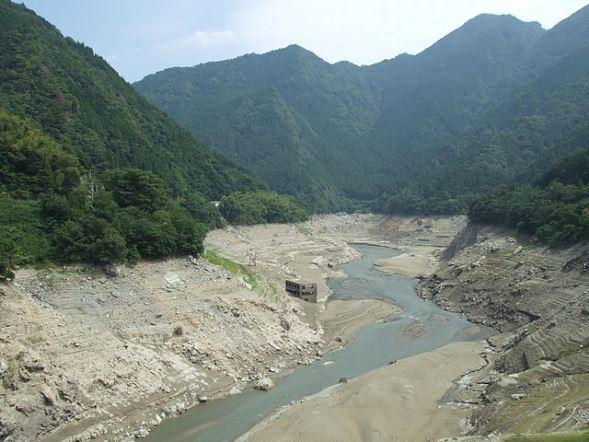 2008年渇水時の早明浦ダム画像。奥に見えるのが旧大川村役場(As6022014さん撮影、Wikimedia Commonsより)