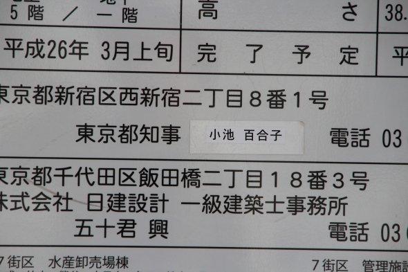 工事看板。東京都知事の項目は、いささか不自然な感じに、シールで「小池百合子」と上書きされている。M記者が「何回も貼り変わっちゃったから......」