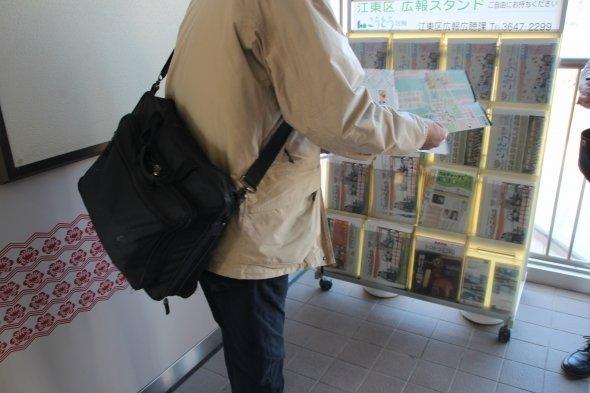 観光パンフレットを手に取るM記者。なお、英語パンフでは豊洲新市場は「11月オープン」と記されていた