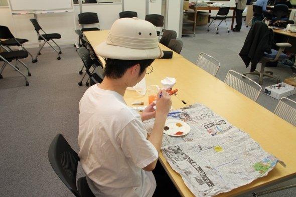 みんなが原稿を書く中、紙粘土で遊ぶT編集長