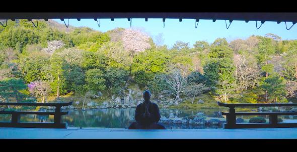 天龍寺・曹源池庭園を前に座禅を組む薬師寺さん(画像提供:iroha records キッサコ)