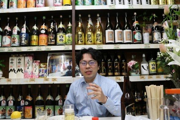 【17時56分】K編集長「1軒目なのに、結構楽しくなってきましたよ」。背後左には「福岡人志、」の写真が。