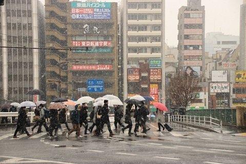 雪が降る中、傘を差し交差点を歩く通勤客ら(2日9時半頃、JR市ヶ谷駅前交差点。Jタウンネット編集部員撮影)