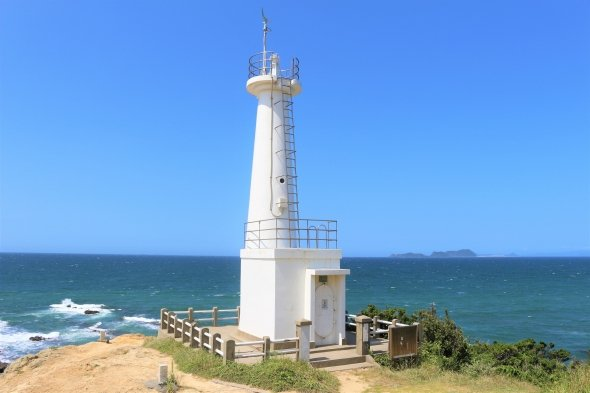 若松区の妙見崎灯台。青い空と海に、白い波と灯台が映える