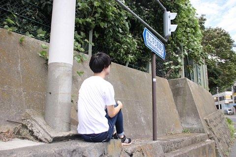 尻で押すほど重い物を持っていなかったので、標識の下で体育座りをして、尻で坂を体感してみた記者。三脚とタイマー機能による撮影後、坂を上ってきた歩行者に訝しげに一瞥された(神奈川県横須賀市にて。以下記者撮影)