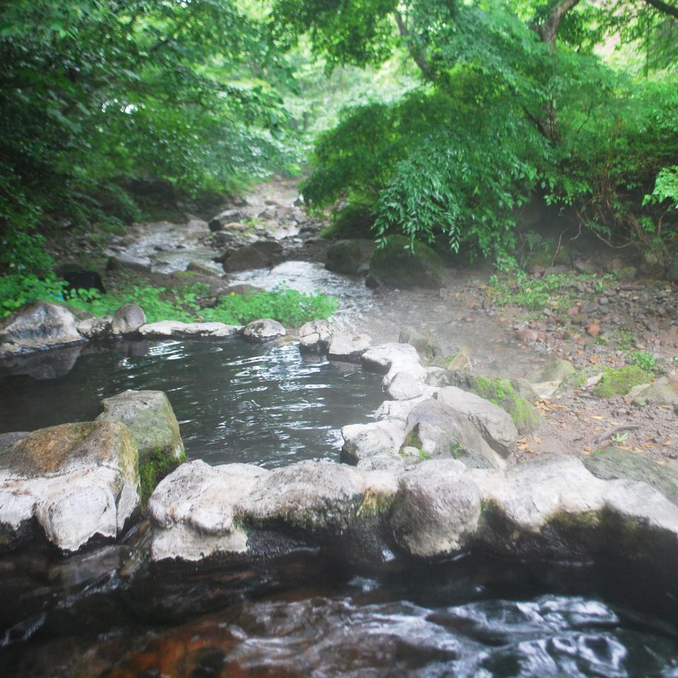 天然の川のすぐ横に野天風呂がある
