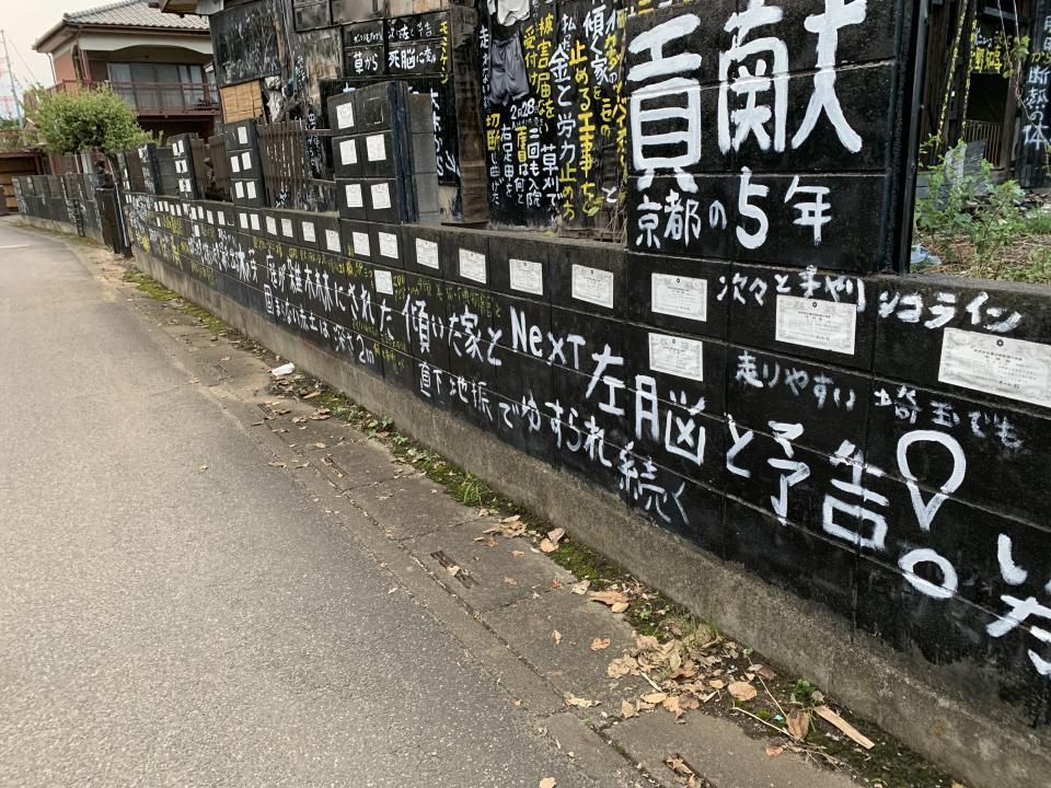 塀の写真。白い紙が株券だ。